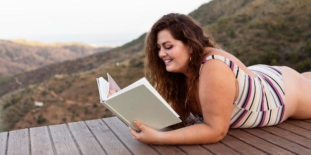 屋外で本を読む女性の側面図