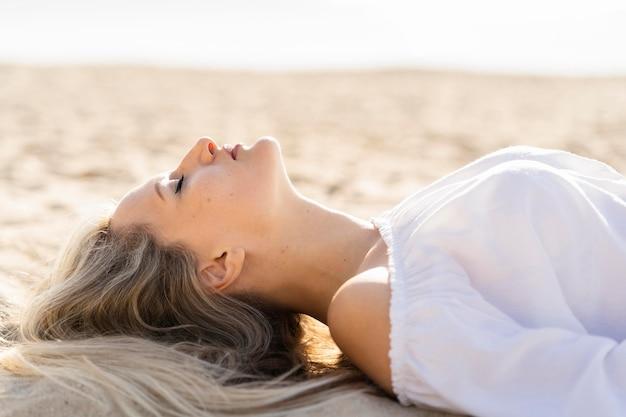 ビーチでリラックスした女性の側面図