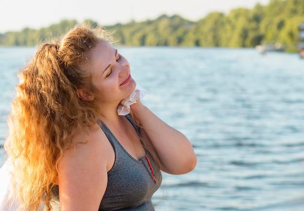 Вид сбоку женщины, отдыхающей после тренировки на берегу озера с копией пространства