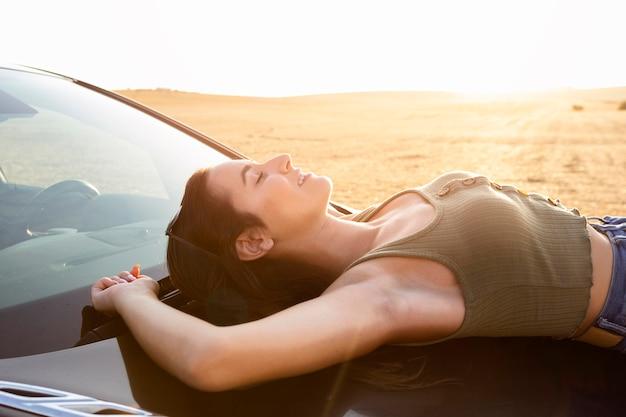 屋外で車で休んでいる女性の側面図
