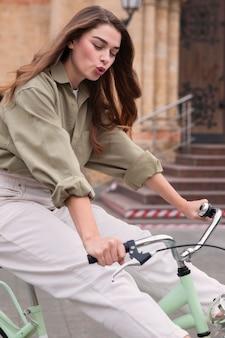 야외에서 도시에서 그녀의 자전거를 타는 여자의 모습