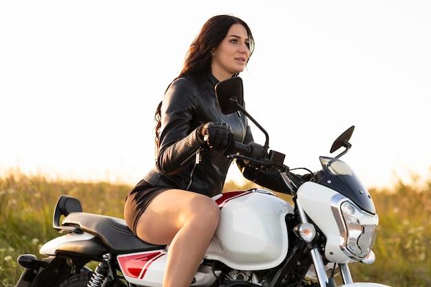 彼女のバイクに屈託のない乗馬の女性の側面図