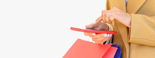 Вид сбоку на женщину, делающую покупки в интернете со смартфоном на киберпонедельник с копией пространства