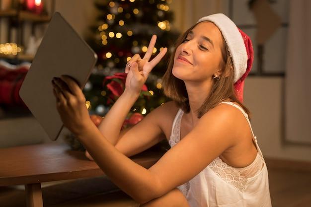 サンタの帽子をかぶってタブレットを保持しながらピースサインを示す女性の側面図