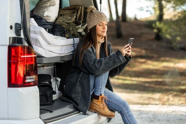 도로 여행 중에 자동차 트렁크에 앉아 스마트 폰을 사용하는 여성의 측면보기