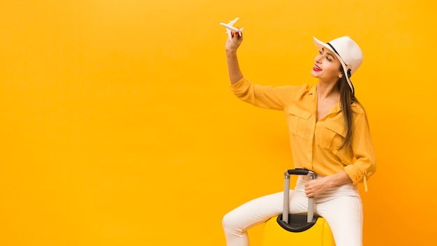 Вид сбоку женщины, сидящей на багаже и держащей плоскую фигурку с копией пространства