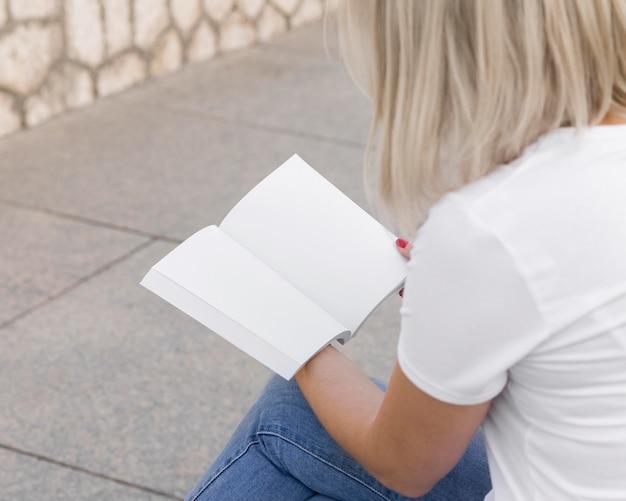 Вид сбоку женщины, сидящей на открытом воздухе и читающей книгу