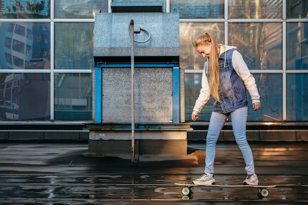 屋外でスケートボードをする女性の側面図