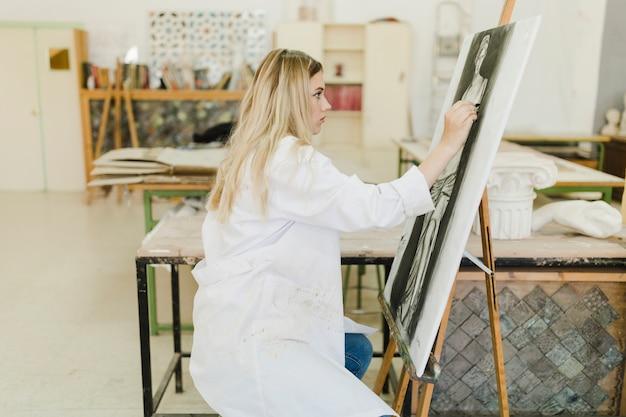 キャンバスに彫刻をスケッチする女性の側面図