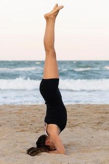 Вид сбоку женщины, стоящей на голове на пляже