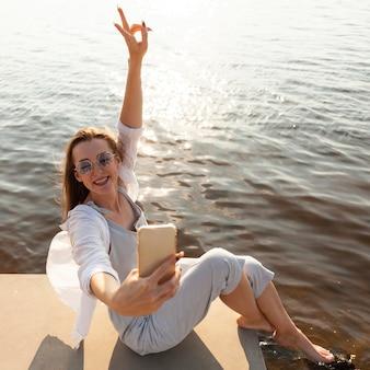 Вид сбоку женщины, делающей селфи на берегу озера