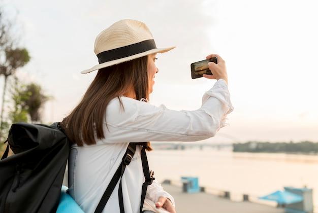 旅行中にスマートフォンで写真を撮る女性の側面図