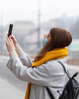 Вид сбоку на женщину, фотографирующую со смартфоном в медицинской маске