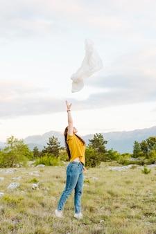 Вид сбоку женщины бросали шарф в воздухе