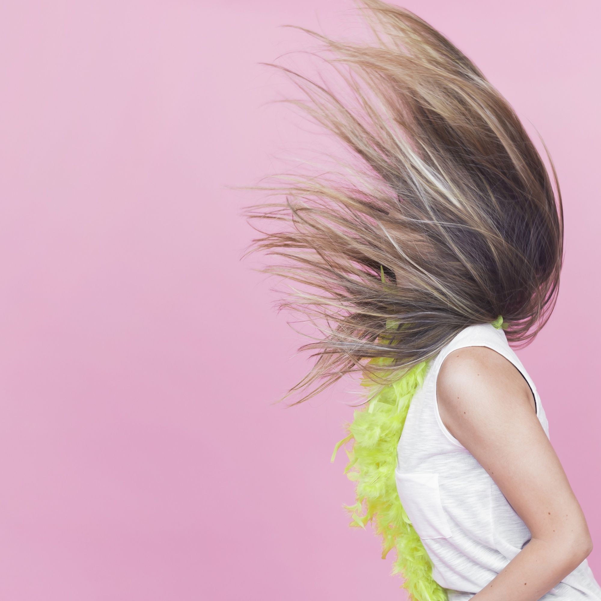 Side view of woman tossing her long hair against pink background