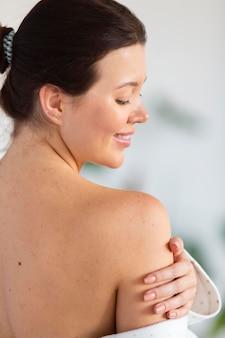 Вид сбоку женщины, касающейся мягкой кожи после ухода за собой