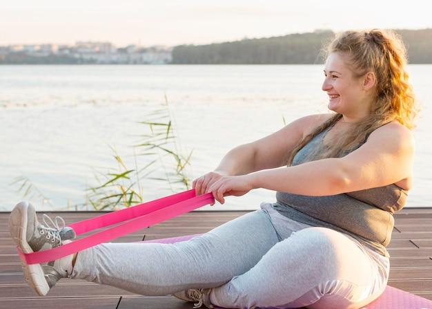 Вид сбоку тренировки женщины с резинкой