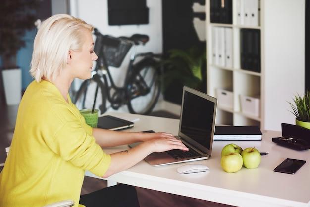 Вид сбоку женщины, печатающей на клавиатуре ноутбука