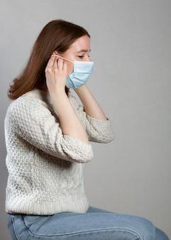보호를 위해 의료 마스크를 사용하는 여성의 측면보기