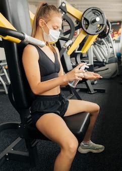 체육관에서 운동하는 동안 손 소독제를 사용하는 여자의 측면보기