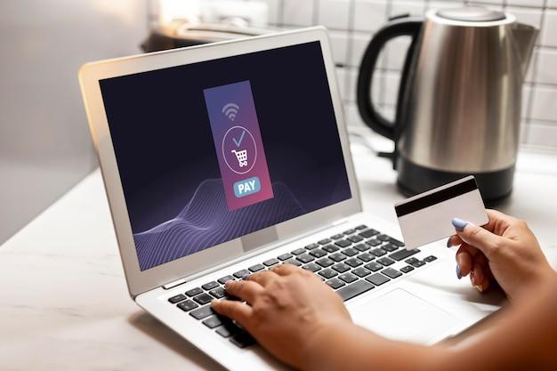 신용 카드로 온라인 쇼핑을 위해 노트북을 사용하는 여성의 측면