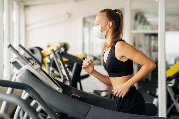 Вид сбоку женщины, использующей беговую дорожку в тренажерном зале