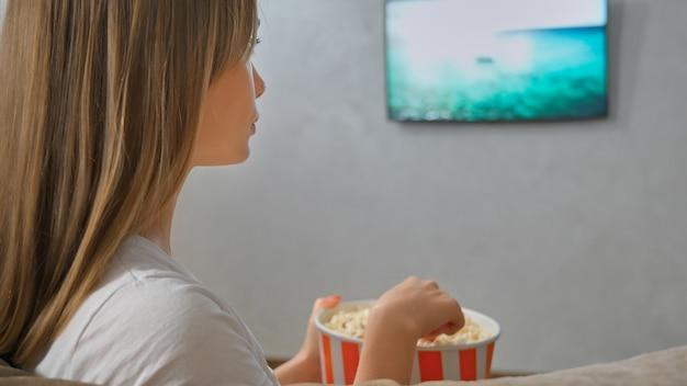 Женщина смотрит телевизор и ест попкорн, вид сбоку.
