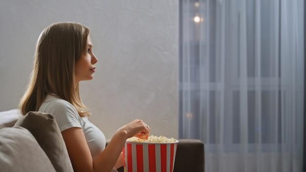 Tv를 시청하는 감탄을 가진 여자의 측면보기.