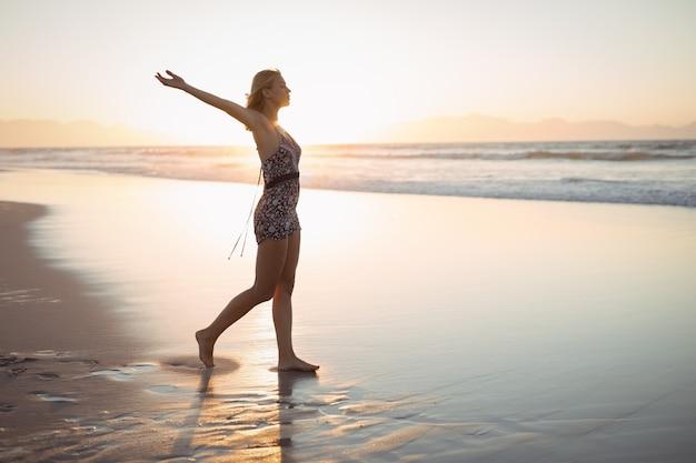 Вид сбоку женщины с раскинутыми руками, стоя на пляже