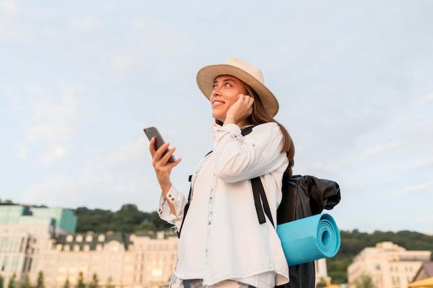 旅行のバックパックとスマートフォンを持つ女性の側面図