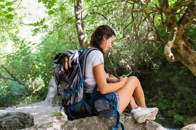 Вид сбоку женщины с рюкзаком, глядя на телефон, исследуя природу