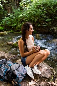 自然を探索しながら休んでいるバックパックを持つ女性の側面図