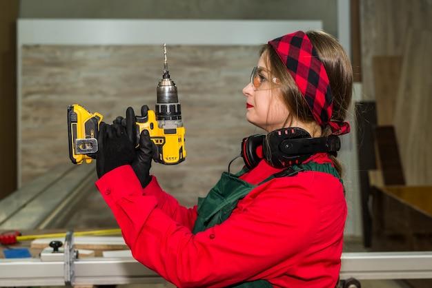 大工仕事でドリルマシンを持つ女性の側面図