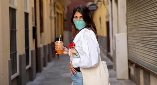 Вид сбоку женщины с маской для лица и продуктовыми сумками