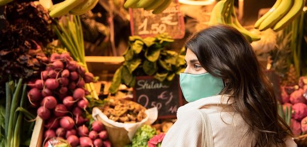 市場でフェイスマスクを持つ女性の側面図
