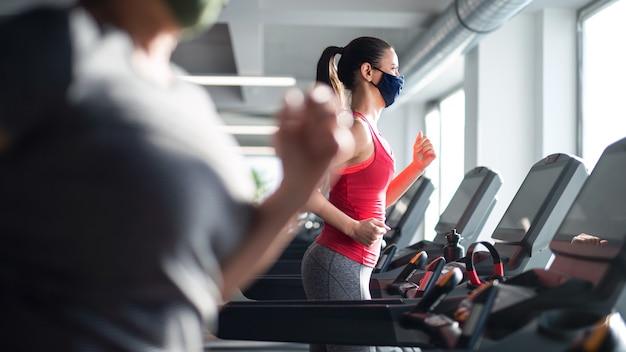 코로나바이러스 개념인 체육관에서 러닝머신에서 운동을 하는 얼굴 마스크를 쓴 여성의 측면.
