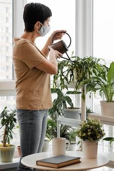 Вид сбоку женщины с маской для лица, поливающей растения в горшках в помещении