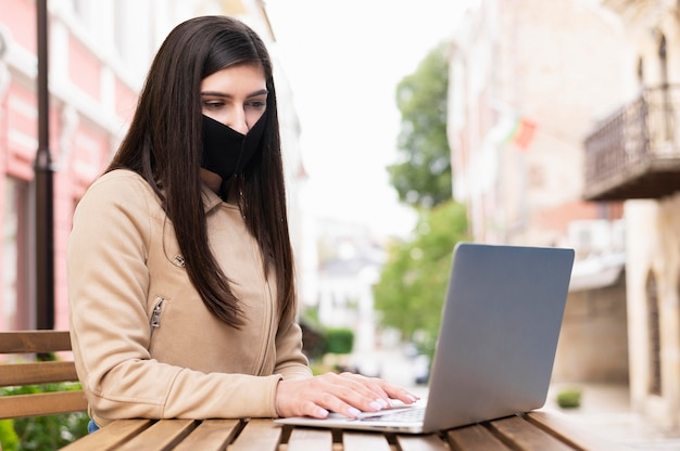屋外のラップトップに取り組んでフェイスマスクを持つ女性の側面図