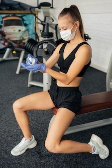 Вид сбоку женщины с перчатками и медицинской маской, использующей дезинфицирующее средство для рук в тренажерном зале