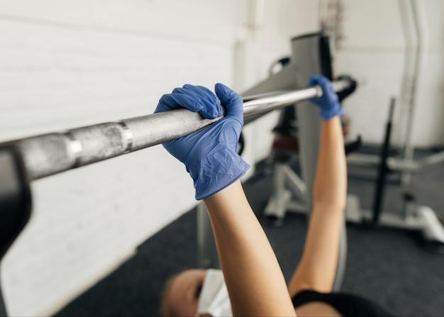 Вид сбоку женщины с перчатками и медицинской маской, тренирующейся в тренажерном зале