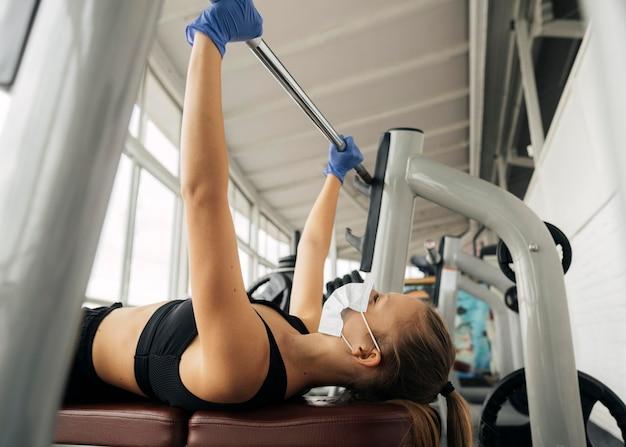 Вид сбоку женщины с перчатками, тренирующейся в тренажерном зале