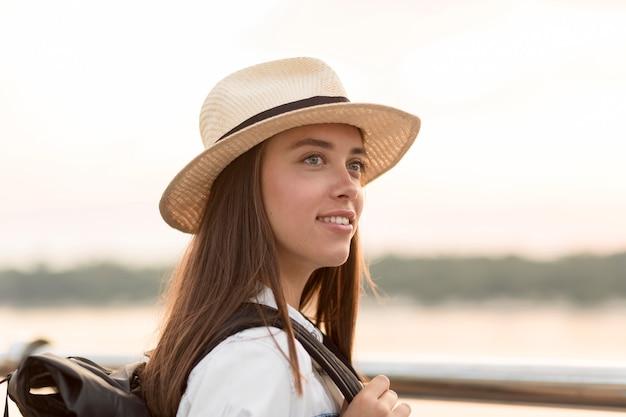 旅行中にポーズの帽子を持つ女性の側面図