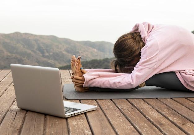 屋外でヨガをしているラップトップを持つ女性の側面図