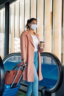 Вид сбоку женщины с багажом и медицинской маской во время пандемии в аэропорту