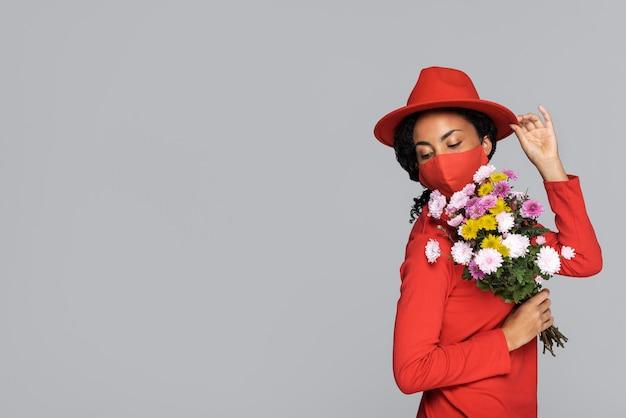 マスクと花を持つ女性の側面図