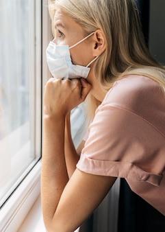 Вид сбоку на женщину с медицинской маской дома, смотрящую в окно во время пандемии