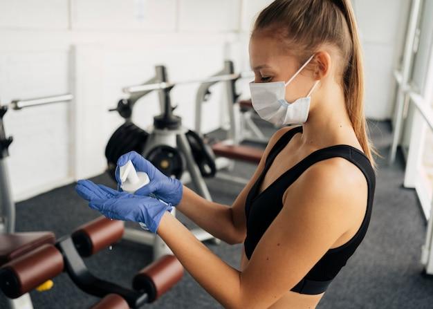 Вид сбоку женщины с медицинской маской в тренажерном зале, используя дезинфицирующее средство для рук на перчатках