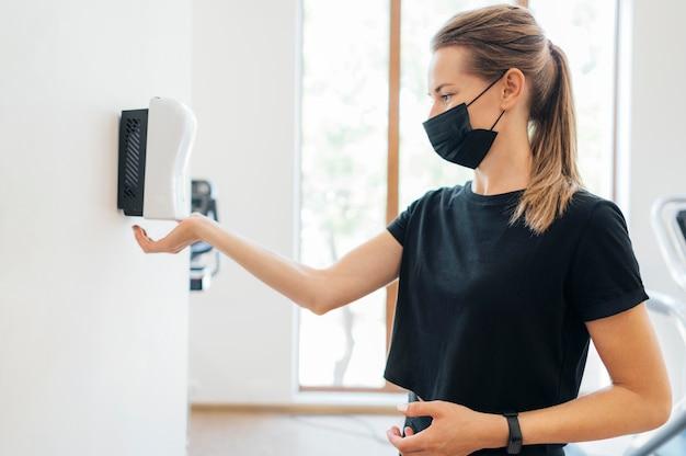 Вид сбоку на женщину с медицинской маской, дезинфицирующую руки в тренажерном зале