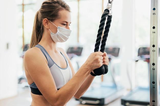 유행병 동안 체육관에서 운동하는 의료 마스크를 가진 여자의 측면보기