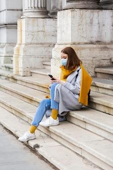 Вид сбоку женщины с медицинской маской, сидящей на ступеньках и использующей смартфон